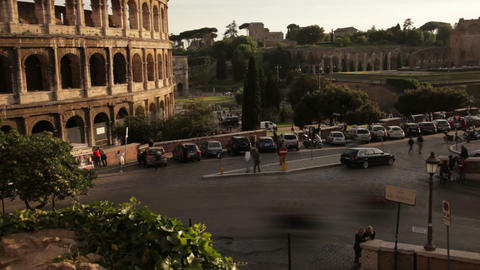 Cars driving by the Colosseum seen from nearby park Footage