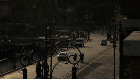 Cars, mopeds, bicycles, and pedestrians on street near the Colosseum Footage