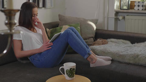 Young woman sits on her couch with her tablet computer Live Action