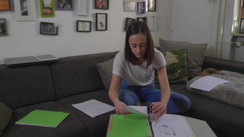 Young woman sorts documents in her living room Footage