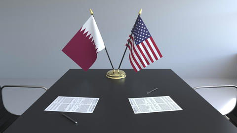 Flags of Qatar and the United States of America and papers on the table Footage