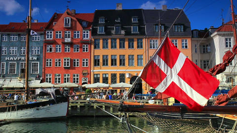 Static shot of old buildings with Danish flag in the foreground in Copenhagen, D Footage