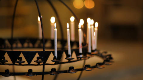 Dolly shot of candles in a candle holder inside a church in Copenhagen, Denmark Footage