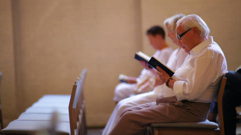 Dolly shot of elderly people reading the bible at a church in Copenhagen, Denmar Footage