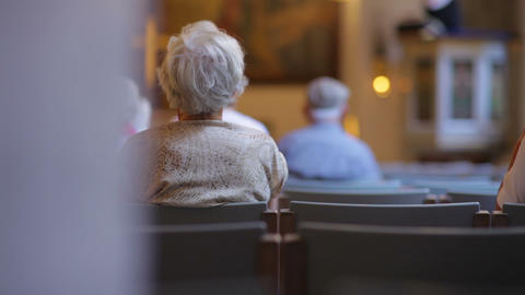 Dolly shot of elderly people worshiping in church Live Action