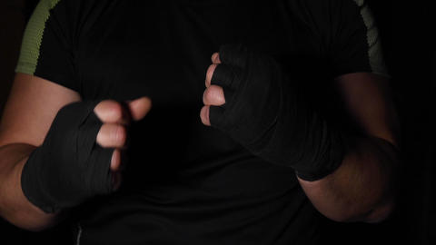 athlete is standing in a boxing rack, his hands are wrapped in a black bandage GIF
