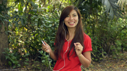 Woman Enjoying Listening to Music on Headphones Smiles at Camera Footage