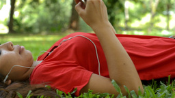 Young Woman Listening To Music While Lying on the Grass Stock Video Footage