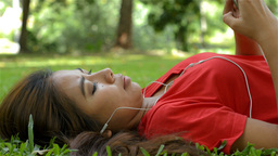 Young Woman Listening To Music While Lying on the Grass Footage