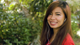 Woman Enjoying Listening to Music on Headphones Smiles at the Camera Footage