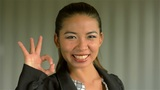 Young Asian Businesswoman Giving a Smiling 'OK' sign to the Camera Footage