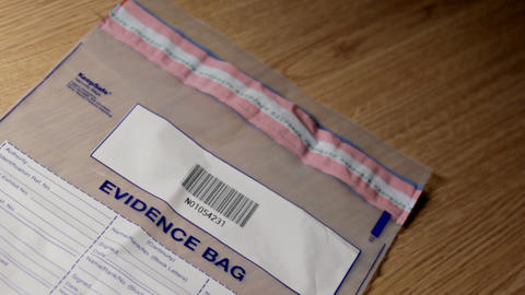 Investigator putting gun into evidence bag Stock Video Footage