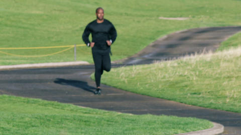 Slow motion shot of a man running down a paved trail Footage