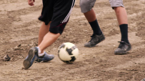 Two boys playing soccer on dirt Footage