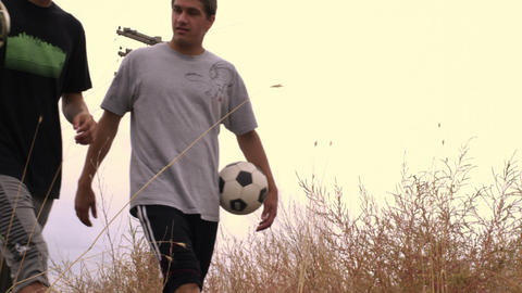 Two boys walking through a field carrying soccer balls Live Action