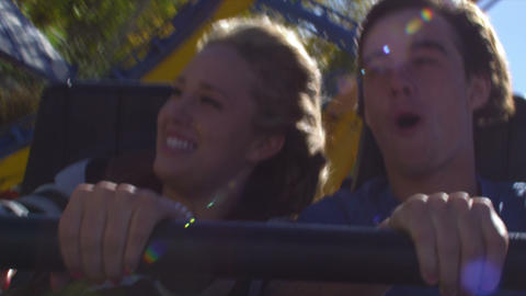 Shot of young couple holding onto safety bar and screaming as coaster goes throu Footage