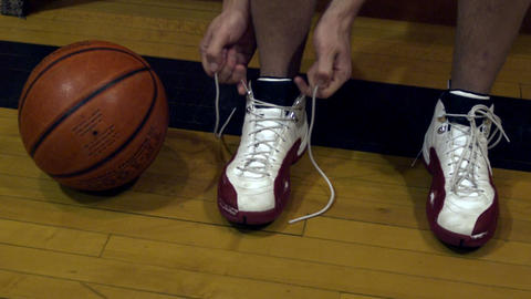 Young man tying basketball shoes Footage