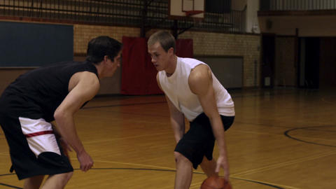 Dribbling a basketball between legs in a one-on-one game Footage