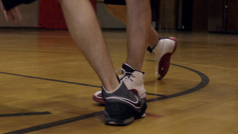 Legs and feet of two people playing basketball Live Action