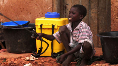 Young boy in Ghana sits pumping water from a container happily Footage