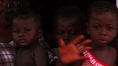 Three children sit looking at the camera next to their mom Footage