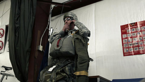 Soldier putting on glasses and strapping on helmet before parachuting Footage