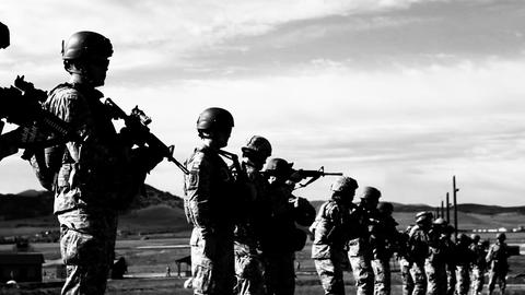 High contrast black and white shot of soldiers practicing firing technique Footage