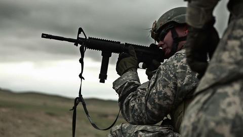 Kneeling soldier shoots M4 rifle in target practice Footage