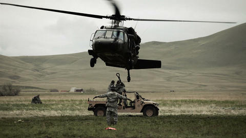 Shot from ground of Black Hawk helicopter hovering above Humvee while soldier gi Footage