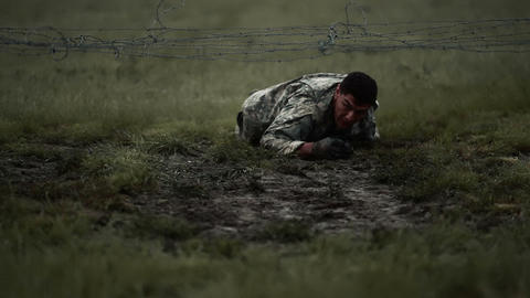 Soldier gets his coat snagged on low barbed wire when crawling under it Footage