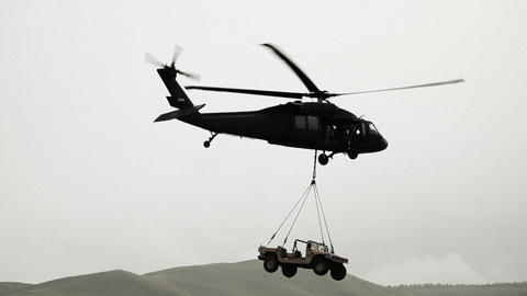 Humvee being hauled by Black Hawk helicopter from field Footage