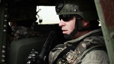 Soldier wearing sunglasses looking out side door of Humvee Footage