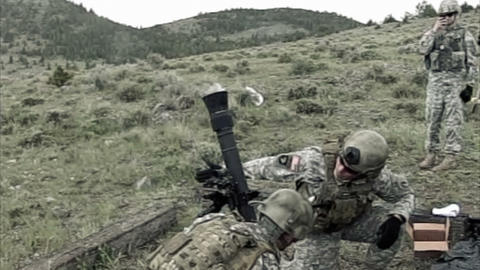 Slow motion clip of mortar team firing, drop mortar into firing possition Footage