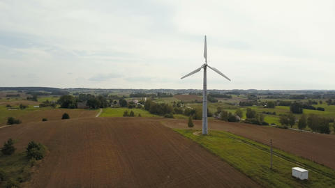 Aerial view of single wind turbine rotating fast. Summer countryside with ビデオ