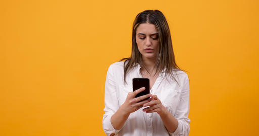 Shoked and emotional young woman looking at the phone Footage
