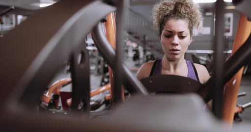 Strong woman working out on weight machine at the gym Footage