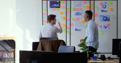 Side view of young cool mixed-race business team planning and working in a modern office 4k Live Action