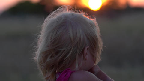 The little girl is watching the sunset. The child admires the setting sun in the Footage