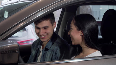 Young happy couple choosing new automobile at dealership salon Live Action