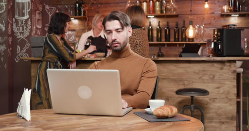 Young entrepreneur having a conversation on his webcam while in a restaurant Live Action