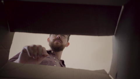 Bearded man in glasses leans over box, opens it and looks inside with interest Footage