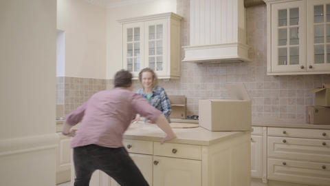 Cheerful man running after woman in the kitchen, man chasing his wife, then Footage