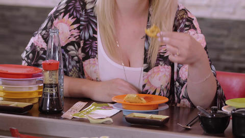 Young woman eats fingerfood in an Asian Sushi restaurant Footage