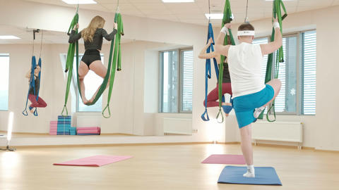Aerial, antigravity yoga in gym. Group of people swinging in the hammocks Footage