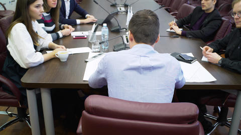 backside view manager holds work meeting with colleagues GIF