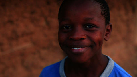 Little Kenyan boy in a blue shirt laughing and smiling Footage