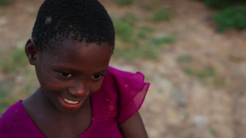 Kenyan girl looking between the camera and the ground Footage