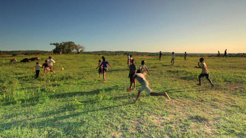 Kids playing soccer in a field in Africa Footage