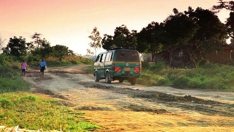 Green van driving on a dirt road near a village in Africa Footage