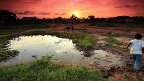 Group of boys playing at village water hole at sunset in Kenya Footage